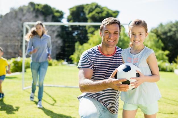 父と娘のサッカーを保持している笑顔の肖像画