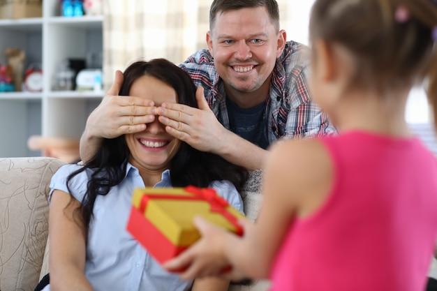 Портрет улыбающегося отца, закрывающего глаза матери. удивленная женщина ждет настоящего. молодая красивая дочь дает подарок маме. счастливая семья и концепция дня рождения