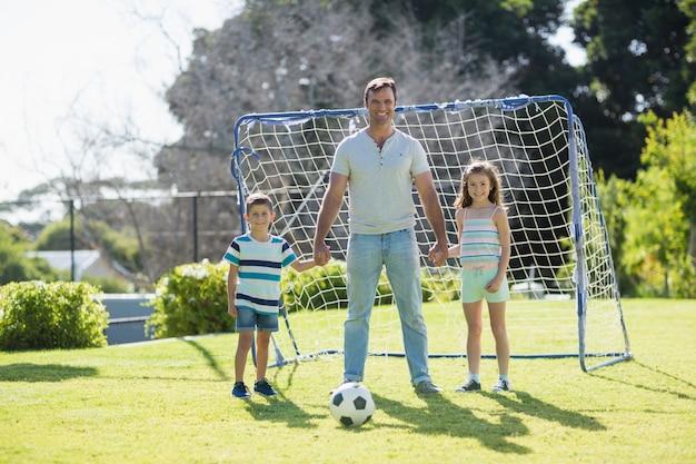 彼の息子と娘と一緒にサッカーをして笑顔の父の肖像