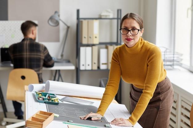 사무실에서 책상에 서있는 동안 청사진과 계획을 그리는 웃는 여성 건축가의 초상화와,