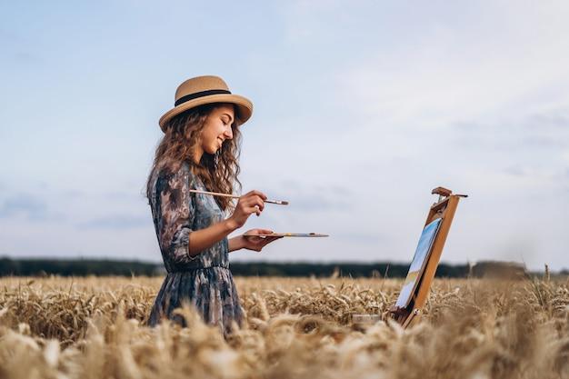 모자에 곱슬 머리를 가진 여성 예술가 미소의 초상화. 소녀는 밀밭에 풍경의 그림을 그립니다. 공간 복사