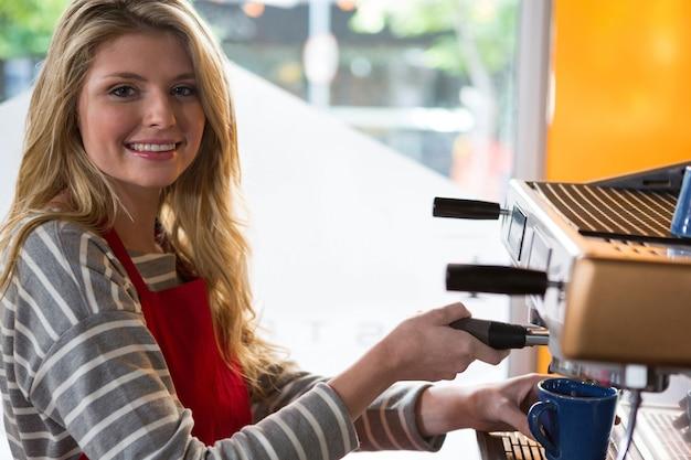 카페테리아에서 기계로 커피를 준비하는 웃는 여성 바리 스타의 초상화