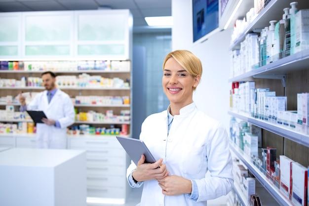 Портрет улыбающегося женского белокурого фармацевта, стоящего в аптеке или аптеке у полки с лекарствами и держащей таблетку.