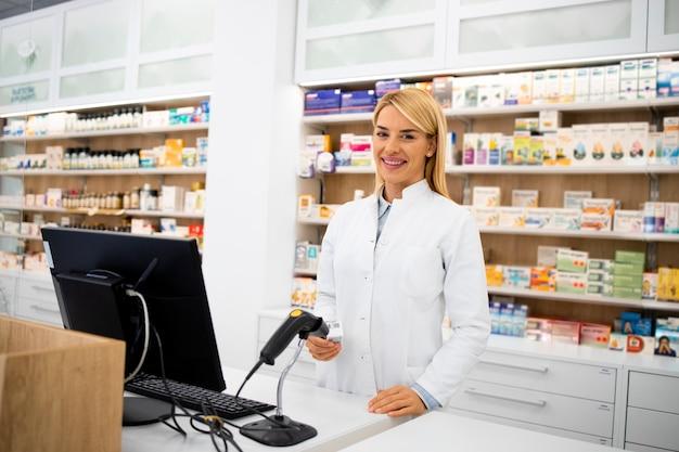 ドラッグストアに立って薬を売っている笑顔の女性白人薬剤師の肖像画。
