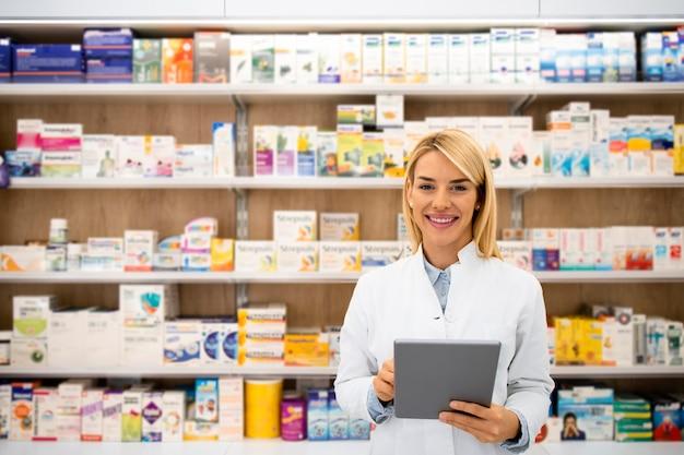 タブレットコンピューターを保持しているドラッグストアに立っている笑顔の女性白人薬剤師の肖像画。