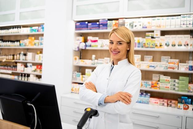 腕を組んでドラッグストアに立っている笑顔の女性白人薬剤師の肖像画。