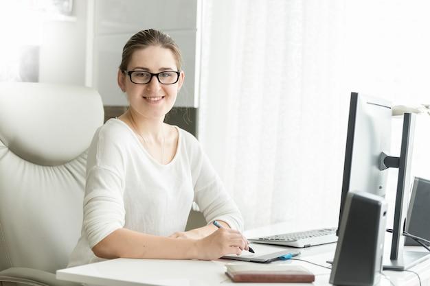 사무실에서 일하는 웃는 여성 디자이너의 초상화