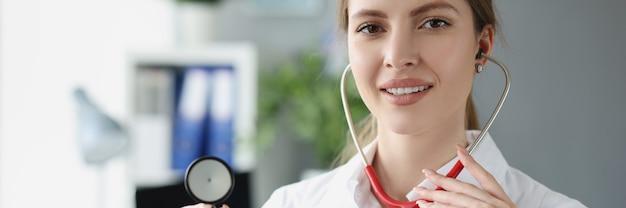 Портрет улыбающейся женщины-врача, держащей стетоскоп крупным планом