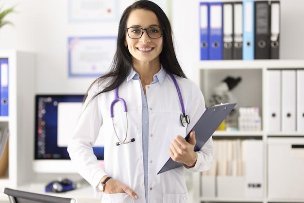 Портрет улыбающейся женщины-врача в белом халате в медицинском кабинете