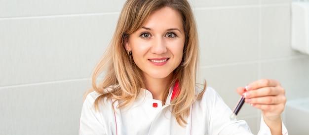 웃는 여성 의사 또는 간호사의 초상화는 혈액 테스트 튜브를 보유하고 있습니다. 좋은 분석의 개념