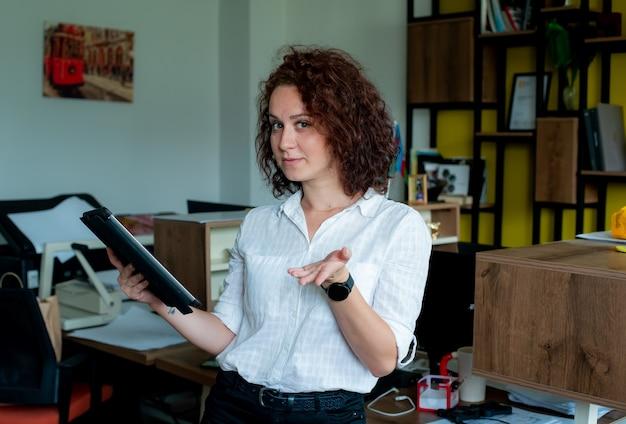 Портрет улыбающейся сотрудницы, держащей планшет, смотрящей в камеру, жестикулирующей рукой, задающей вопрос, выглядящей уверенно, стоя в офисе