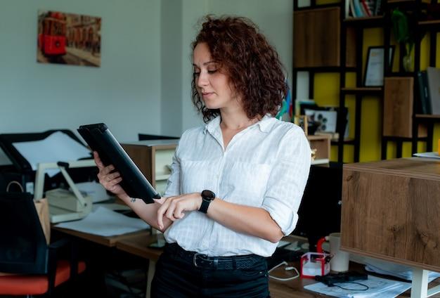 사무실에 서있는 얼굴에 자신감이 미소로보고 태블릿을 들고 웃는 여성 직원의 초상화