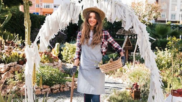 園芸工具および庭のバスケットに立っている笑顔の女性庭師の肖像画