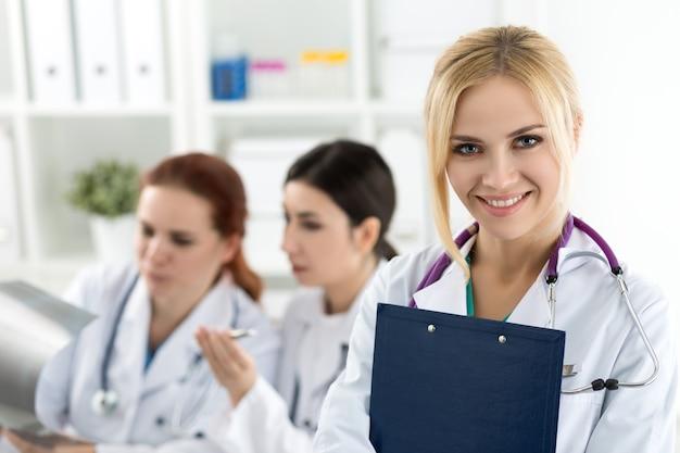 Портрет улыбающегося женского доктора медицины, держащего синюю папку для документов с двумя коллегами, смотрящими на рентгеновское изображение. концепция здравоохранения и медицины.