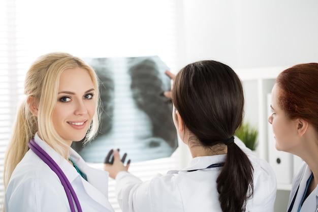 Портрет улыбающегося врача женской медицины с двумя коллегами, смотрящими на рентгеновский снимок. концепция здравоохранения и медицины.
