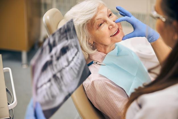 Портрет улыбающейся пациентки, сидящей на стоматологическом кресле, в то время как женщина-врач трогает лицо клиента