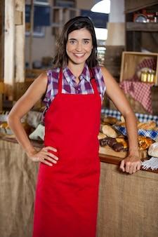 ベーカリーショップで腰に手で立っている笑顔の女性スタッフの肖像画