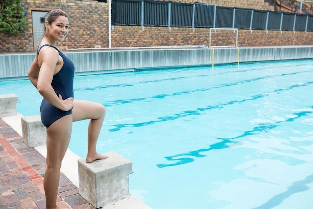 수영장에서 엉덩이에 손으로 서 웃는 여성 수영의 초상화