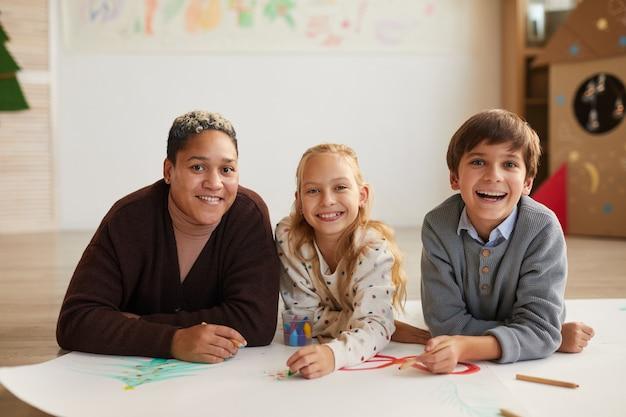 Портрет улыбающейся учительницы, лежащей на полу и смотрящей в камеру с двумя детьми, рисующими картинки, наслаждаясь художественным классом на рождество, скопируйте пространство