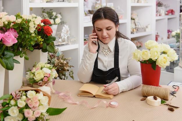 店内で電話で話している花屋の笑顔の肖像画。花の配達。