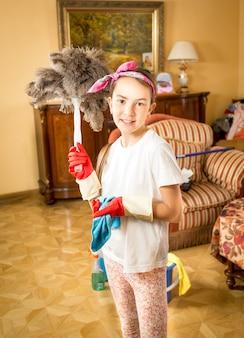 羽ブラシでポーズをとって掃除をしている笑顔の女の子の肖像画