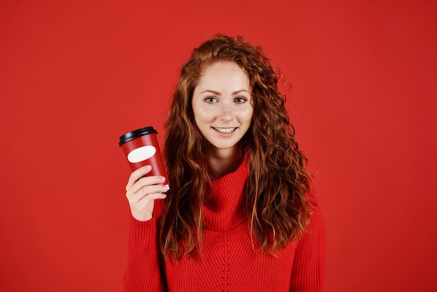 Портрет улыбающейся девушки, держащей одноразовую кружку кофе