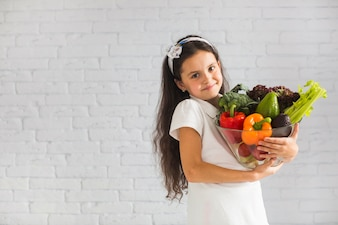 Portrait of smiling girl holding fresh vegetables in big glass bowl