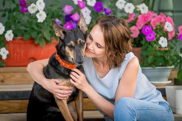 大きな面白い子犬を抱き締める笑顔の女の子の肖像画