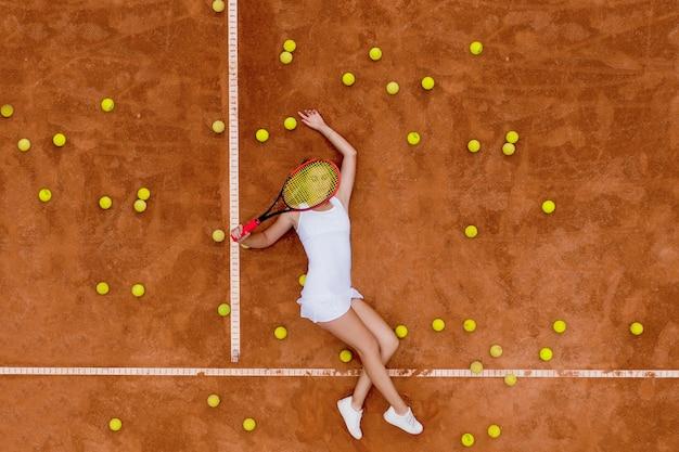 Портрет улыбающейся девушки, расслабляющейся на теннисном корте с большим количеством мячей и ракеткой после тяжелого тенниса