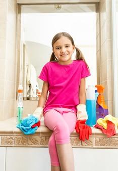 掃除をしながら浴室の流しに座っている笑顔の女の子の肖像画