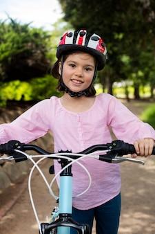 공원에서 자전거와 함께 서 서 웃는 여자의 초상화