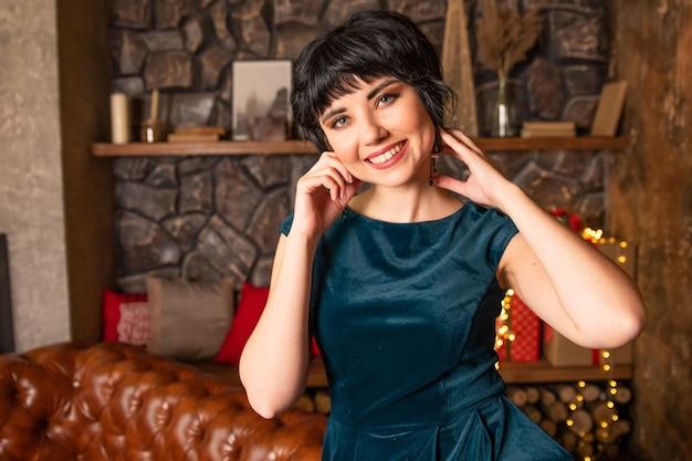 ドレスのソファに座っている笑顔の女の子の肖像画。トレンディな色のタイドウォーターグリーンのドレス。背景にプレゼント