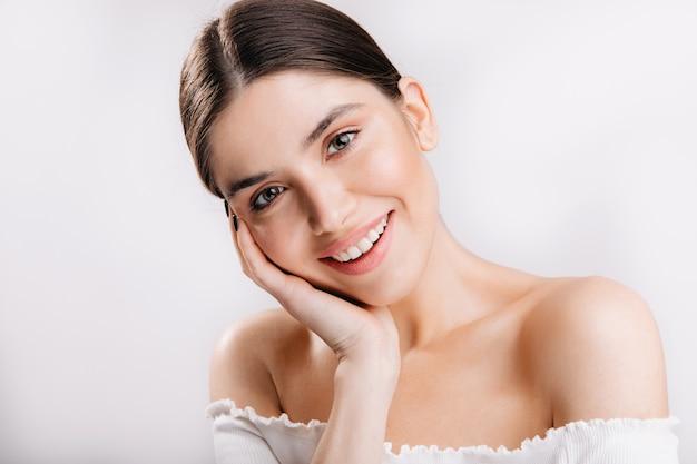 건강한 피부와 웃는 여자의 초상화입니다. 흰 벽에 귀여운 검은 머리 여자.