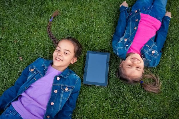 デジタル タブレットで草の上に横たわる笑顔の女の子の肖像画