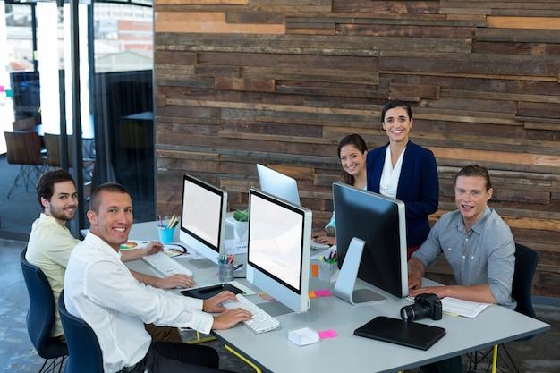 Портрет улыбающихся графических дизайнеров во время работы на персональном компьютере