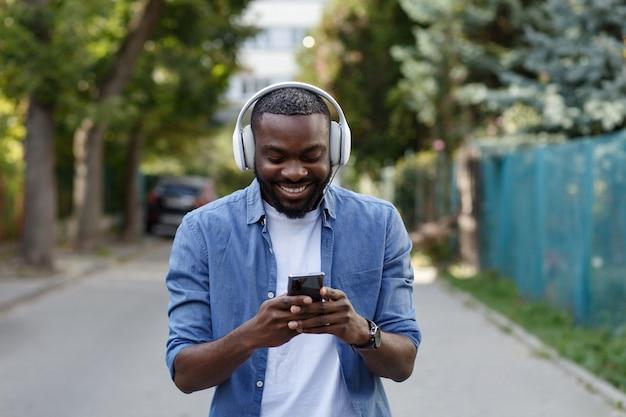 屋外のイヤホンや携帯電話で笑顔の男の肖像画