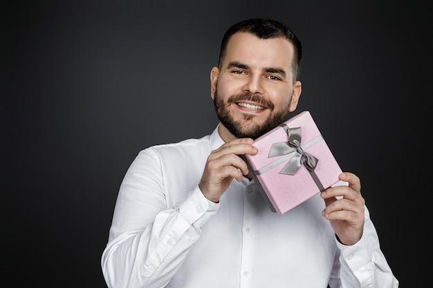 Портрет улыбающегося красивого бородатого мужчины в белой рубашке, держащего подарочную коробку и смотрящего в камеру, изолированного на черном фоне