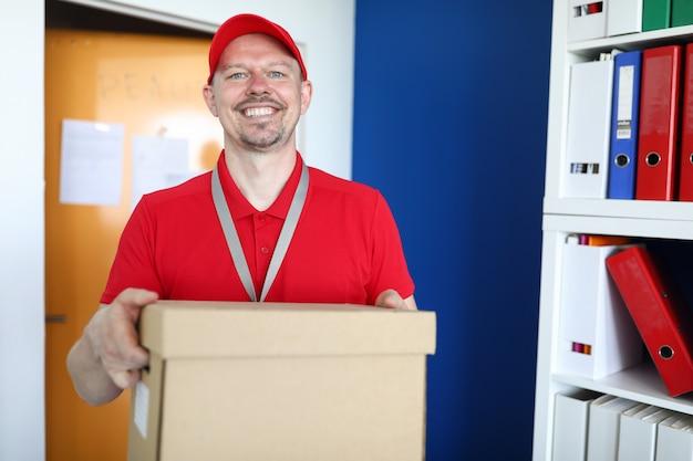 ハンサムな配達人を笑顔の肖像画。大きな箱を保持している宅配便。クライアントへのプロフェッショナルで迅速な配信パッケージ。赤い制服を着た中年男性。オンラインショッピングのコンセプト