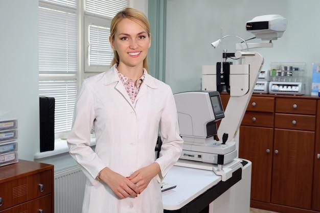 Портрет улыбающегося красивого глазного врача, стоящего с офтальмологическим устройством в кабинете.
