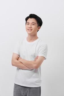 灰色の背景に分離された腕を組んで立って、白いtシャツでハンサムな男の笑顔の肖像画