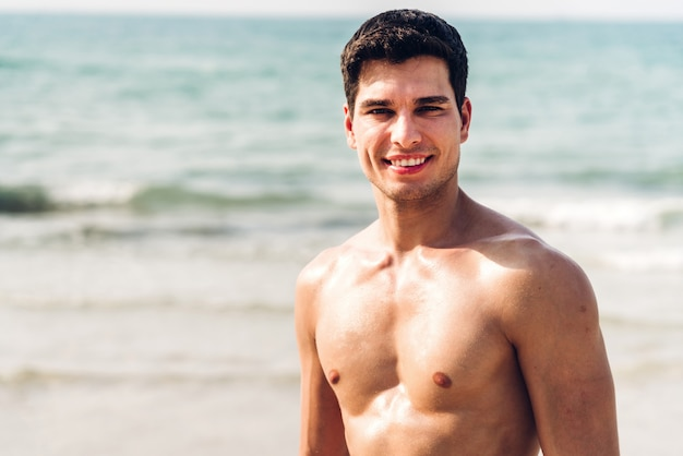 Портрет улыбающегося красивый сексуальный мужчина, показаны мускулистое тело в форме стоя на тропическом пляже. летние каникулы