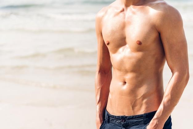 Портрет улыбающегося красивого сексуального человека, показывающего мускулистое пригодное тело, стоящее на тропическом пляже. летние каникулы