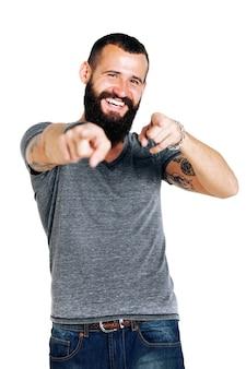 흰 벽 위에 당신을 가리키는 웃는 잘 생긴 문신 수염 남자의 초상화