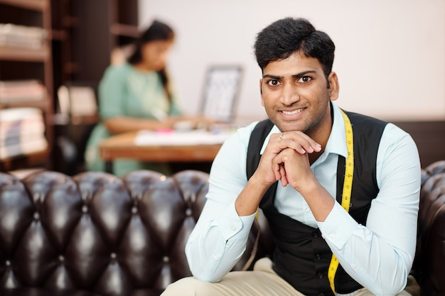 아틀리에 소파에 앉아 테이프를 측정하여 웃는 잘 생긴 젊은 인도 재단사의 초상화