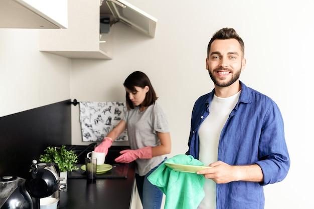 Портрет улыбающегося красивого молодого человека в повседневной рубашке, стоящего на кухне и вытирающего тарелку, помогая подруге мыть посуду