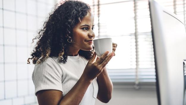 テーブルの上に座っている間デスクトップコンピューターの技術を使用してリラックスした笑顔の幸せなアフリカ系アメリカ人の黒人女性の肖像画。