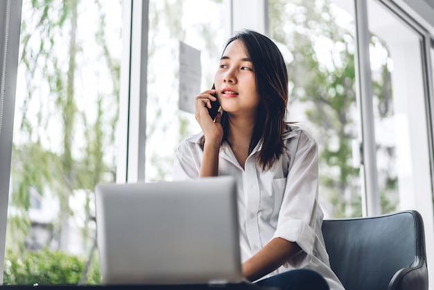 スマートフォンの技術を使用してリラックスし、椅子に座っている間ウィンドウで見て幸せな美しいアジアの女性を笑顔の肖像画。