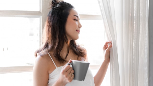 Портрет усмехаясь счастливой жизнерадостной красивой довольно азиатской женщины ослабляя выпивающ и смотрящ чашку горячего кофе или чая. валка девушки наслаждается позавтракать в каникулах утра каникул на кровати дома
