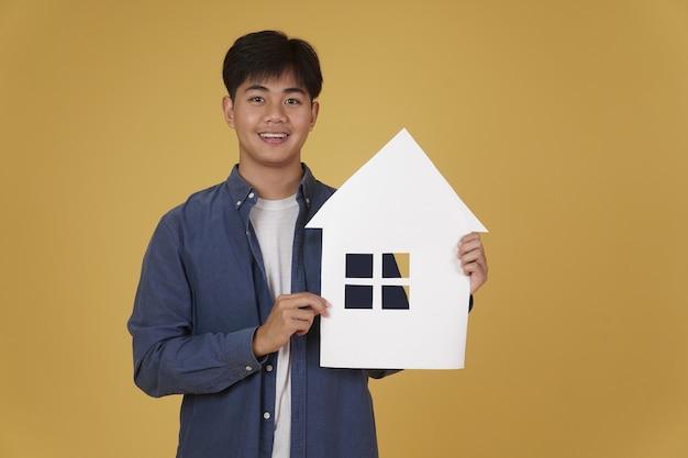 孤立したホームハウスの紙の切り抜きでさりげなく服を着て笑顔幸せな陽気な若いアジア人の肖像画。不動産購入のコンセプト