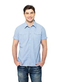 青いカジュアルシャツで笑顔の幸せなハンサムな男の肖像画-白い壁に分離